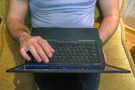 A man works with a laptop touching the screen with his fingers Imagens