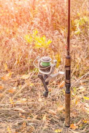 Fishing rod with a coil on the background of autumn grass. Selective focus