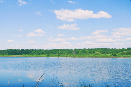 The blue sky with the clouds above the clear blue lake. Summer landscape