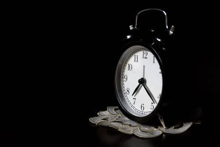 Classic mechanical alarm clock on dark background. Low key Stock Photo