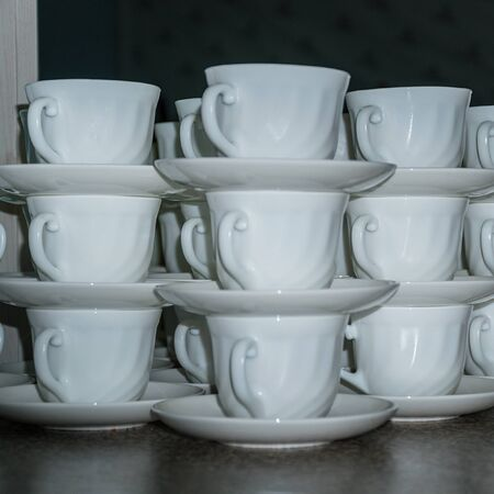White coffee cups with saucers in stacks