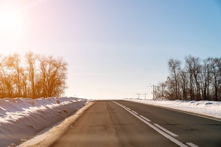 Winter road on the background of the sun in the blue sky