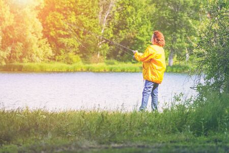 Woman in yellow jacket fishing spinning on the lake in sunlight Imagens