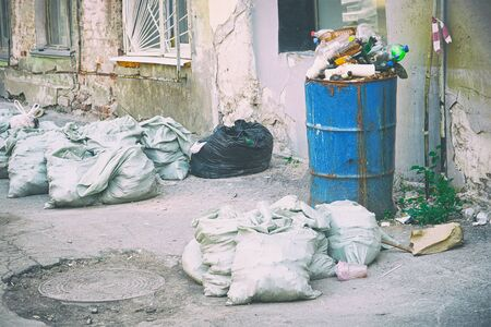 Garbage in bags and barrels on the streets Imagens