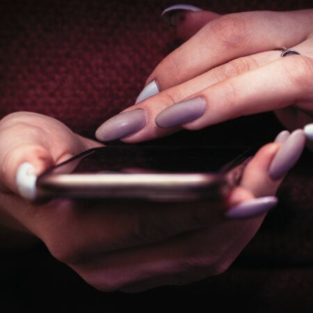 The girl touches her fingers to the phone screen. The girl has a manicure with false nails