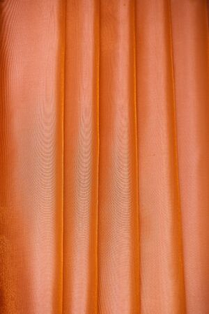 Vertical folds on orange organza curtains for background and design Imagens