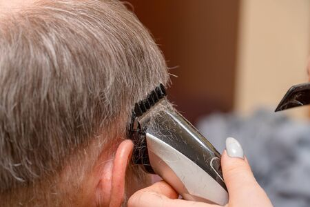 Woman Hairdresser cuts mans hair with electric clipper trimmer. Selective focus