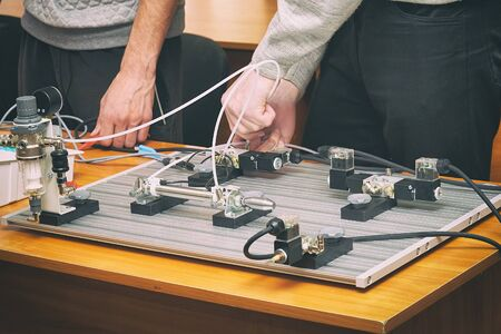 Engineers connect wires control panel with a small test bench for experiments