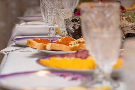Festive table setting with crystal glasses and plates. Sandwiches with red caviar on the table. Selective focus