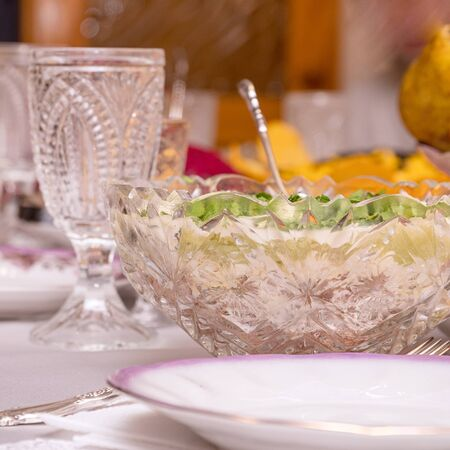 Festive table setting with crystal glasses and plates. Selective focus
