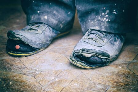 Old torn boots on the mans feet. Boots with holes. Selective focus