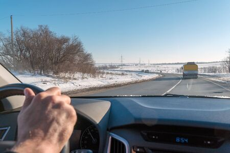 Hand on the steering wheel of the car. View from the windshield. The highway in the winter. Selective focus