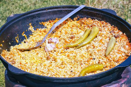 Traditional delicious pilaf with vegetables in a cauldron