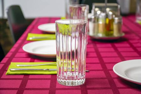 White plate, glass, fork and knife on a napkin. Red tablecloth Banco de Imagens