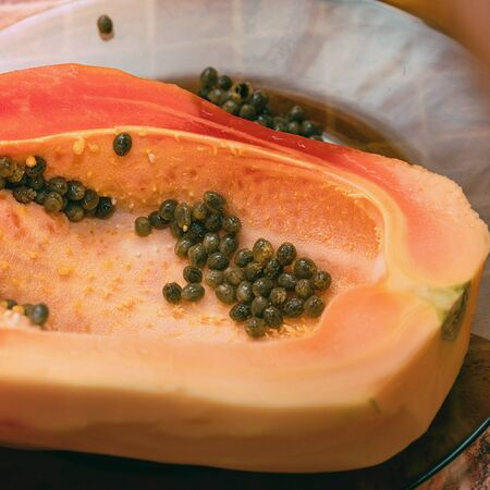 Cut into two parts papaya fruit with seeds. Papaya cut in half