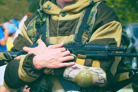 A soldier in camouflage uniform holding a machine gun