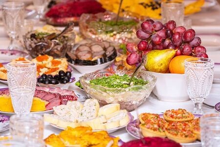 Served table. Snacks, fruits, sandwiches, salads, caviar and slicing on the holiday table. Selective focus