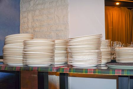 Clean white plates stacked on the table