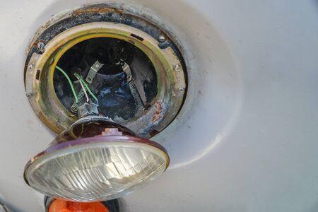 Broken car headlight hanging on the wires. Selective focus Imagens