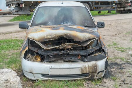 Burnt car on the street. Front view