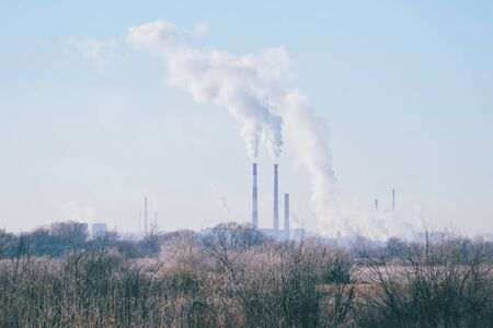 Modern landscape with factory pipes at a distance from which smoke is polluting the air. Environmental pollution.