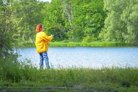 Woman in yellow jacket fishing spinning on the lake