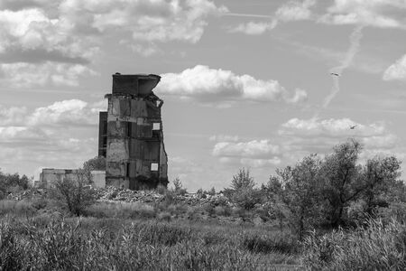 The remains of the ruins of the old building against the cloudy sky. Black and white photo