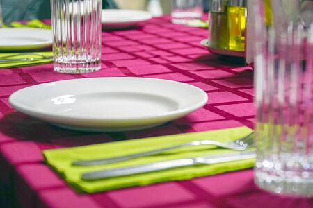 White plate, glass, fork and knife on a napkin. Red tablecloth Imagens