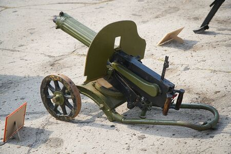 Old green machine gun on the asphalt