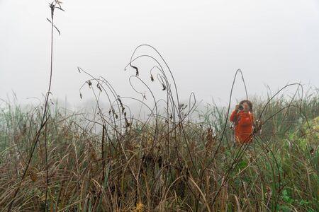 Woman photographer photographs the fog on the lake Imagens