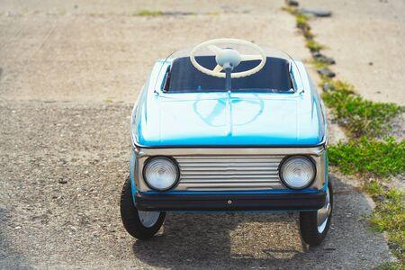 Old childrens car for riding on the asphalt
