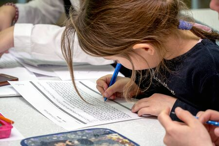 Chapaevsk, Samara region, Russia - October 15, 2019: Elementary school of the city of Chapaevsk. Schoolgirl writes in a notebook