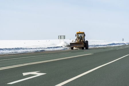 Snowplow cleans the highway from snow on a frosty day Stock Photo