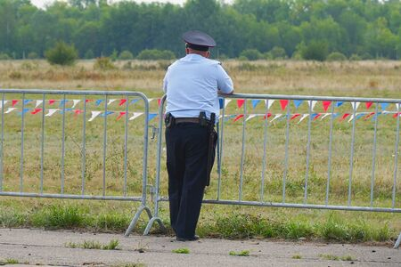Samara, Russia - August 17, 2019: Alone male police officer stands at the barrier fence. Rear view