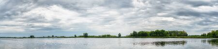 Panorama of the lake with a forest on the opposite shore on a cloudy day
