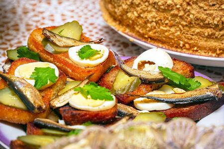 Sandwiches with smoked sprats, boiled egg, pickles and parsley on a plate. Selective focus Stock Photo