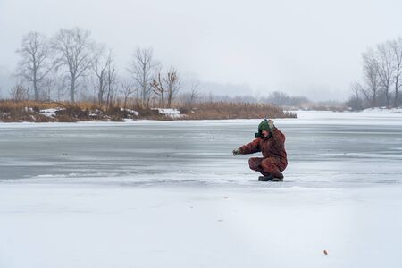 A fisherman sits on the ice of a frozen river and catches fish. Winter Ice fishing