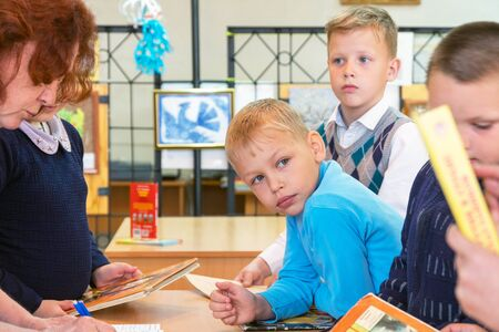 Chapaevsk, Samara region, Russia - May 06, 2019: Elementary school of the city of Chapaevsk. A group of young schoolchildren stand with books at the table. Selective focus