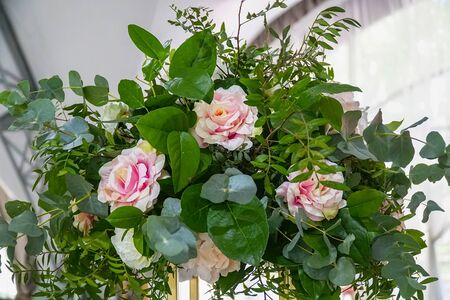 Beautiful bouquet of artificial pink roses and green leaves