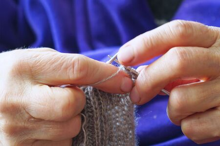 Woman knits a scarf of gray wool with knitting needles. Selective focus