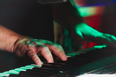 Hands of A pianist or keyboardist of a rock band close up playing a synthesizer. Selective focus 版權商用圖片