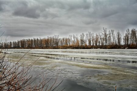 Spring ice drift and melting ice on the river. Spring flood on the river. High water. Spring landscape Stock Photo