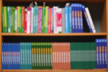 BLURRED VIEW. Books on a shelf in the library. Selective focus