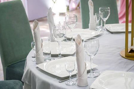 The table in the restaurant is served for dinner. On a table with a white tablecloth, empty wine glasses, a plates, napkins. Selective focus Imagens