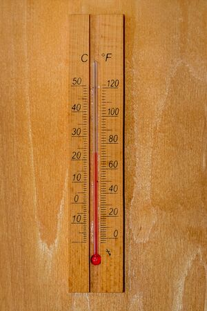 Wooden thermometer on a wooden wall