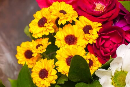 A beautiful bouquet of yellow chrysanthemums and red roses. Background of flowers