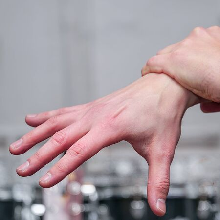 The man holds his hand by the wrist. Joint pain, hand massage Banque d'images