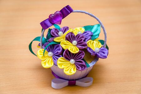 Artificial violets in a small vase on a wooden background or table