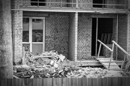 Construction debris next to a red brick house under construction. Garbage on the construction site. Black and white photo Foto de archivo