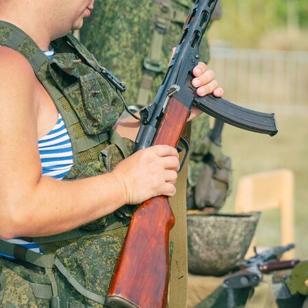A soldier holds an old Russian machine gun from the second world war